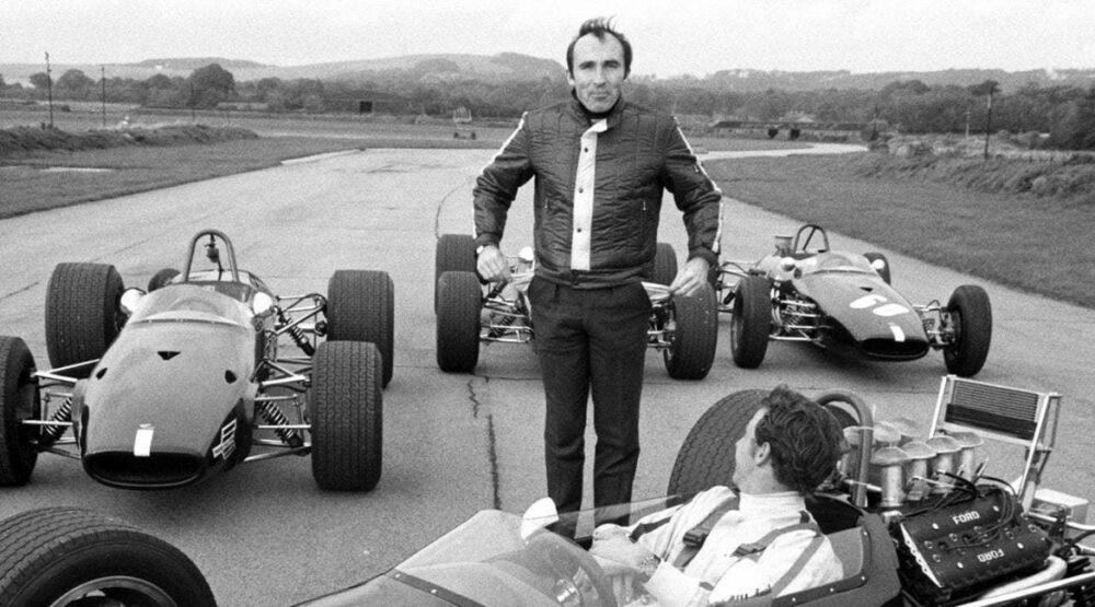 Sir Frank Williams ao lado dos carros de corrida da F1