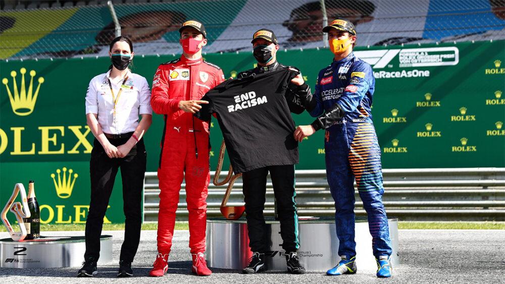 Podio do GP da Austria de F1 com os pilotos segurando blusa com os dizeres 'end racism'